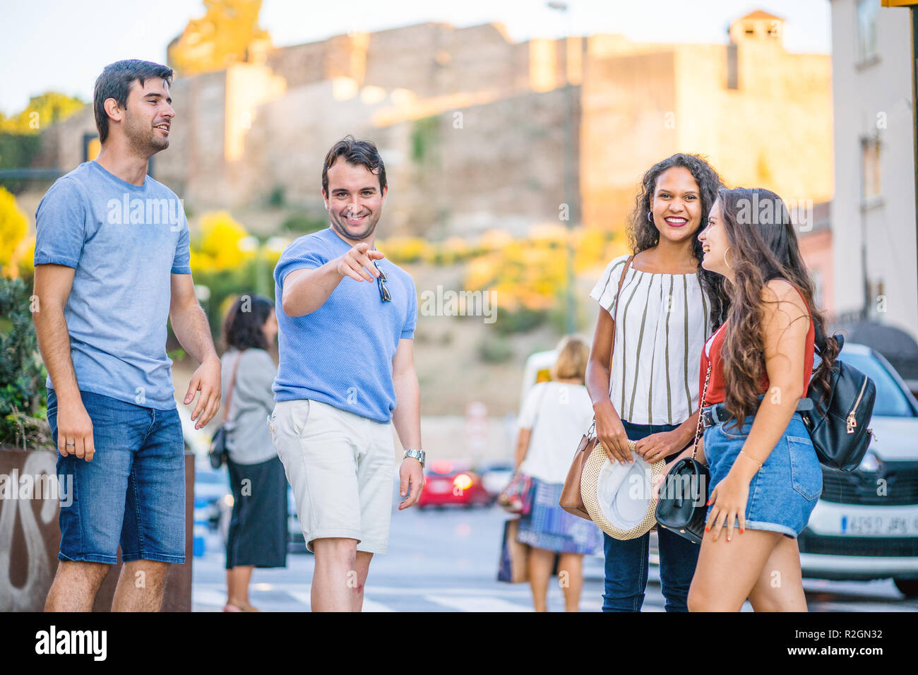 Happy four friends hanging out in the afternoon in the city - Stock Image