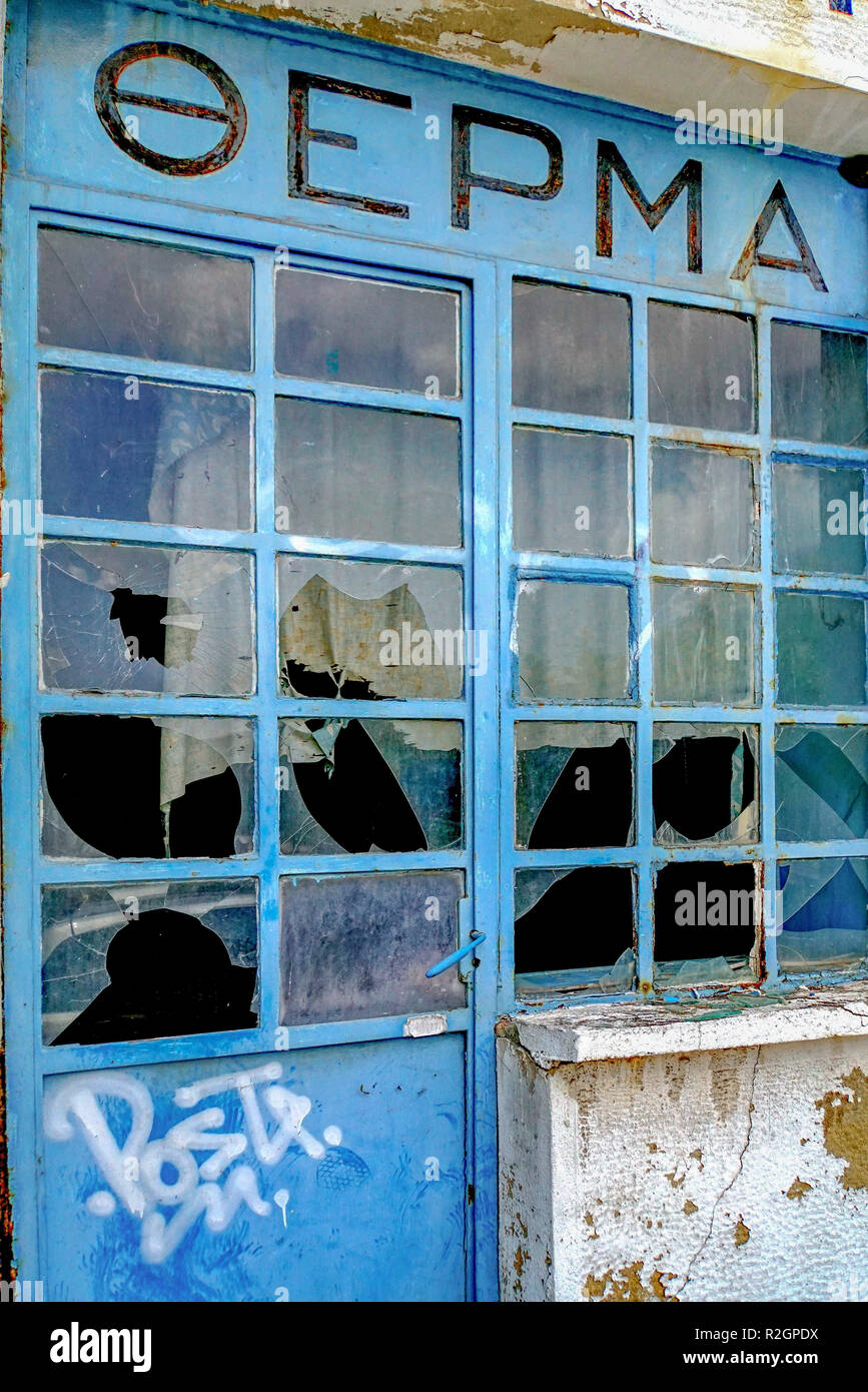 Deserted and dilapidated store front with broken window panes. Economic hardship and depression. Photographed in Athens, Greece - Stock Image