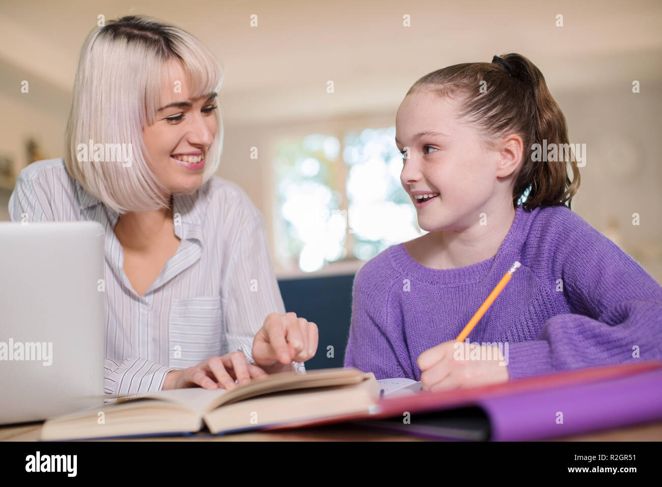 Female Home Tutor Helping Young Girl With Studies - Stock Image