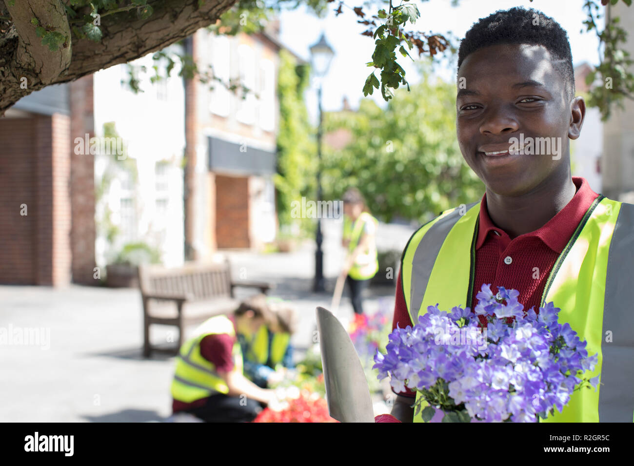 Group Of Helpful Teenagers Planting And Tidying Communal Flower Beds - Stock Image