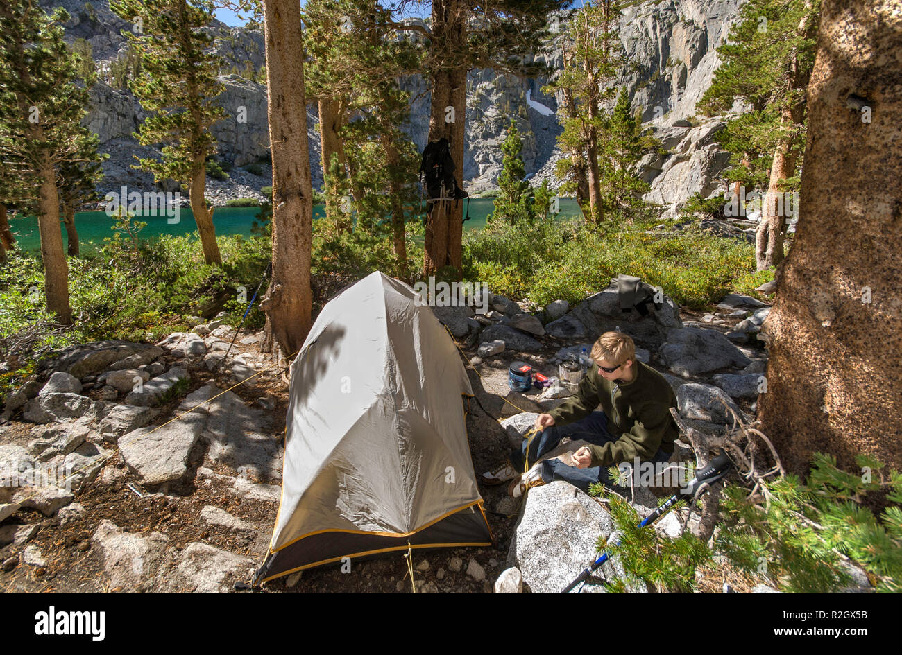 Young hiker at campsite at Brainard Lake, The Palisades region, John Muir Wilderness, Eastern Sierra Nevada, California, USA - Stock Image