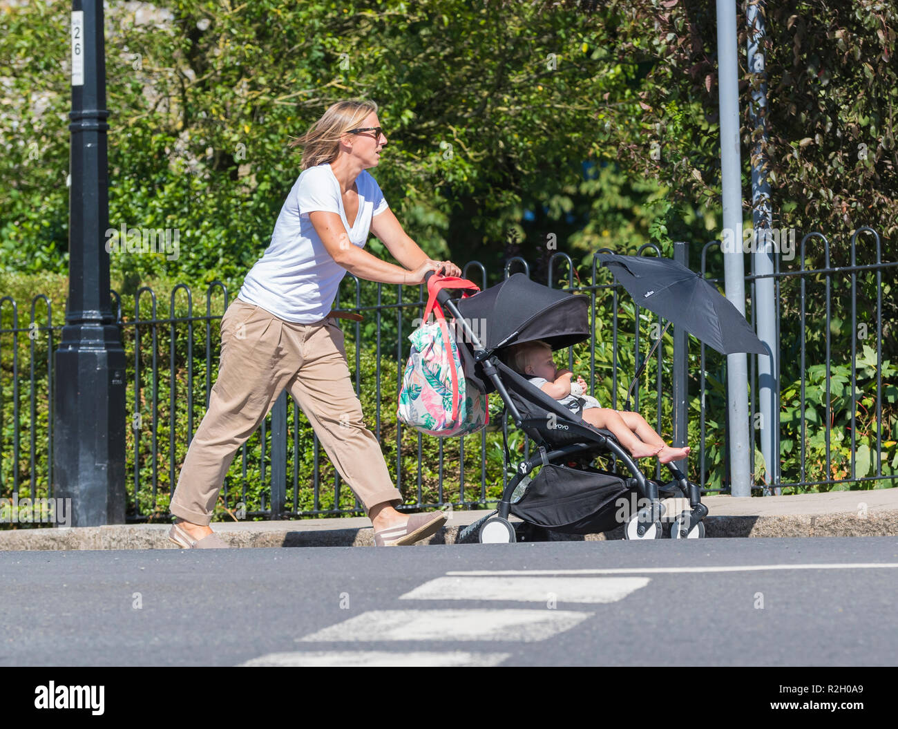 Woman in 30s or 40s pushing child in pushchair with sun protection umbrella to shade kid from sun, in Summer in the UK. - Stock Image