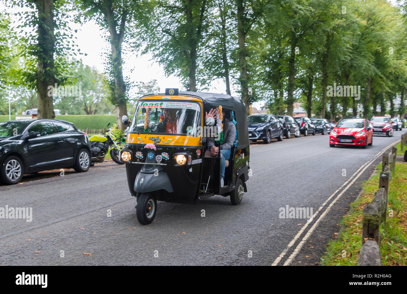 People having a tour in a Piaggio Ape City 3 wheeled cart (commonly known as a Tuk Tuk vehicle) from in Arundel, West Sussex, UK. - Stock Image