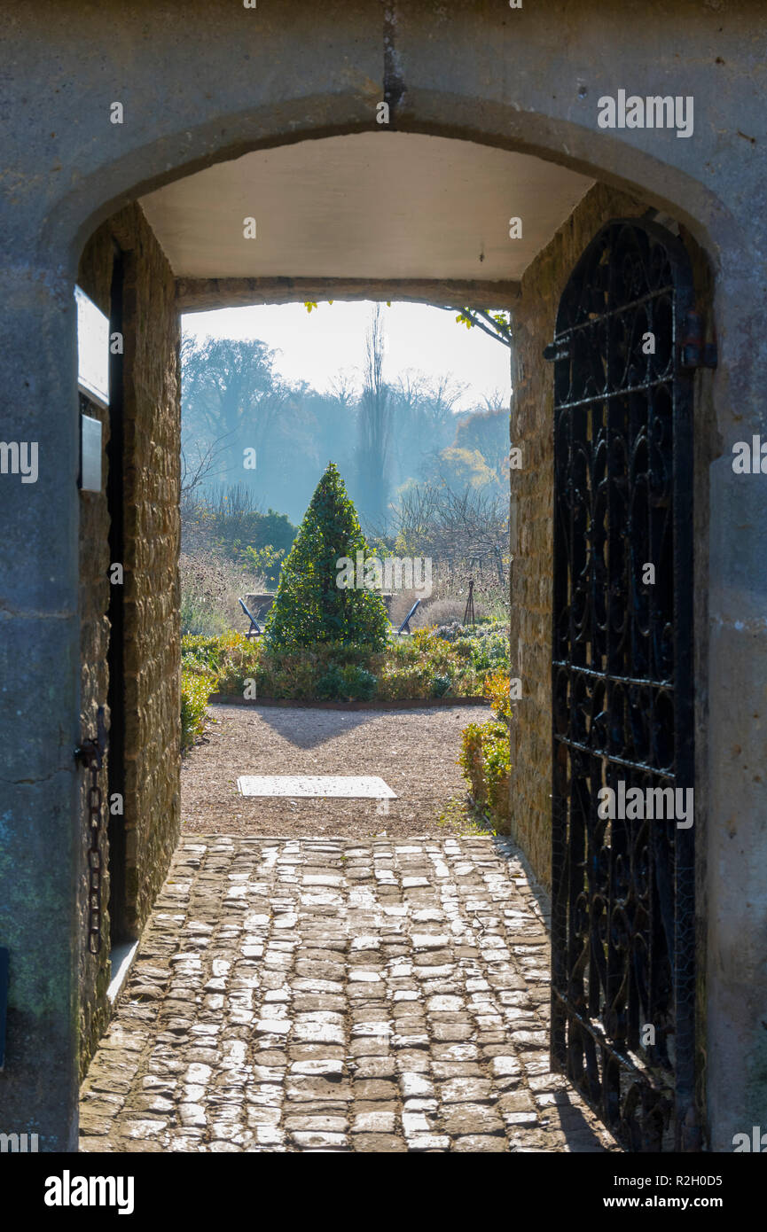 Narrow passageway through to some gardens with an open gate in the UK. Secret garden concept. - Stock Image