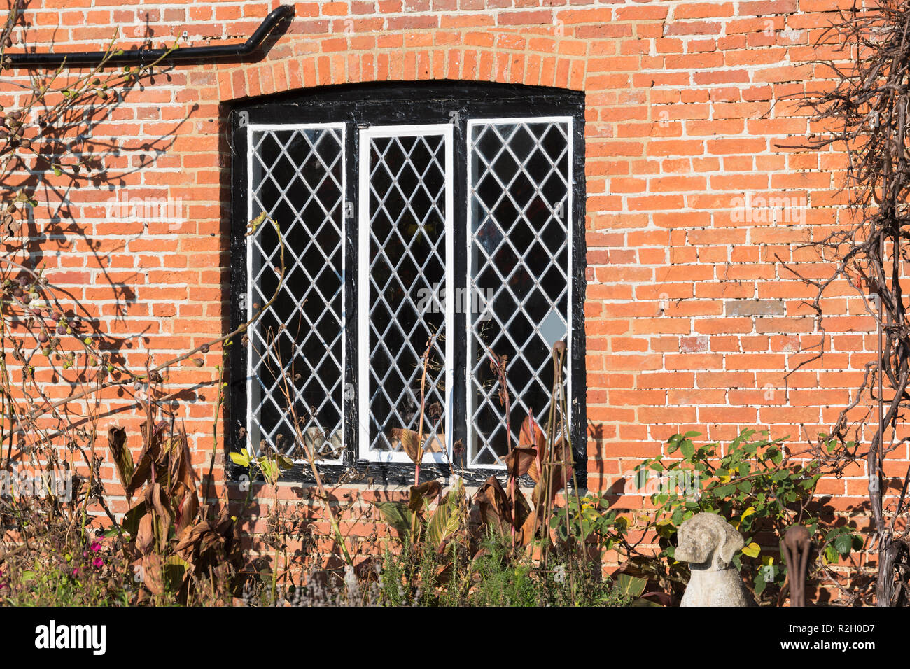 Diamond shaped leaded framed glass window on a wall made of red brick, in the UK. Lead diamond frames windows. - Stock Image