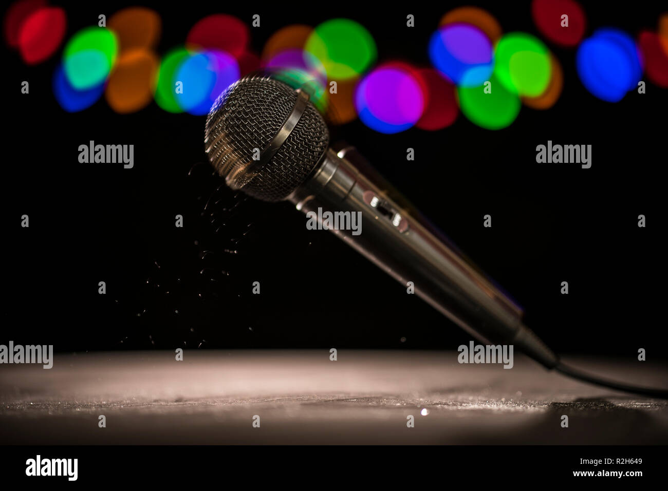 Mic Drop! A microphone falling onto a stage floor. - Stock Image