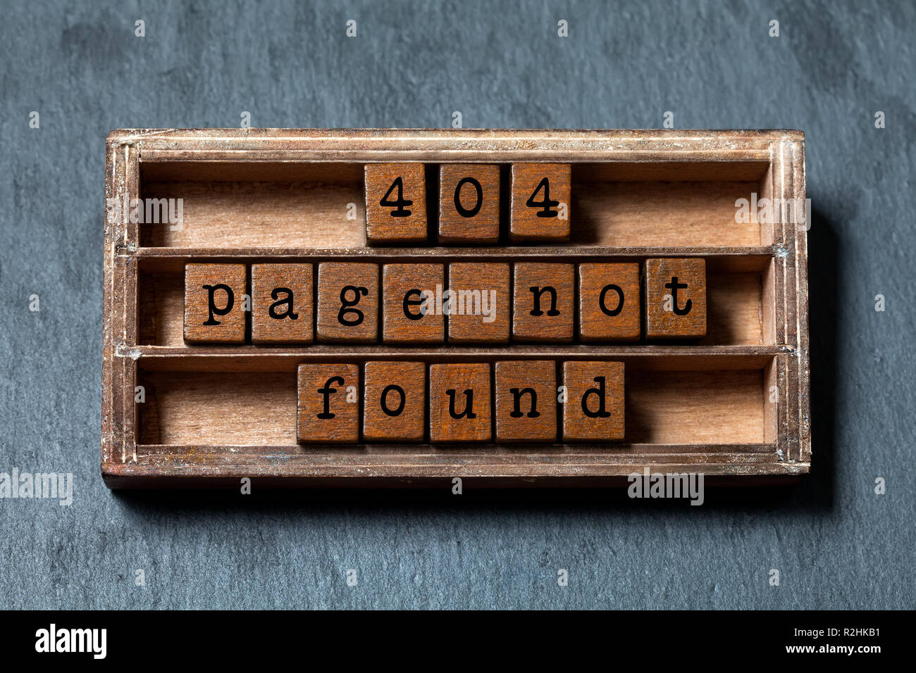 Error 404 page not found concept. Vintage box, wooden cubes with old style letters. Gray stone textured background - Stock Image