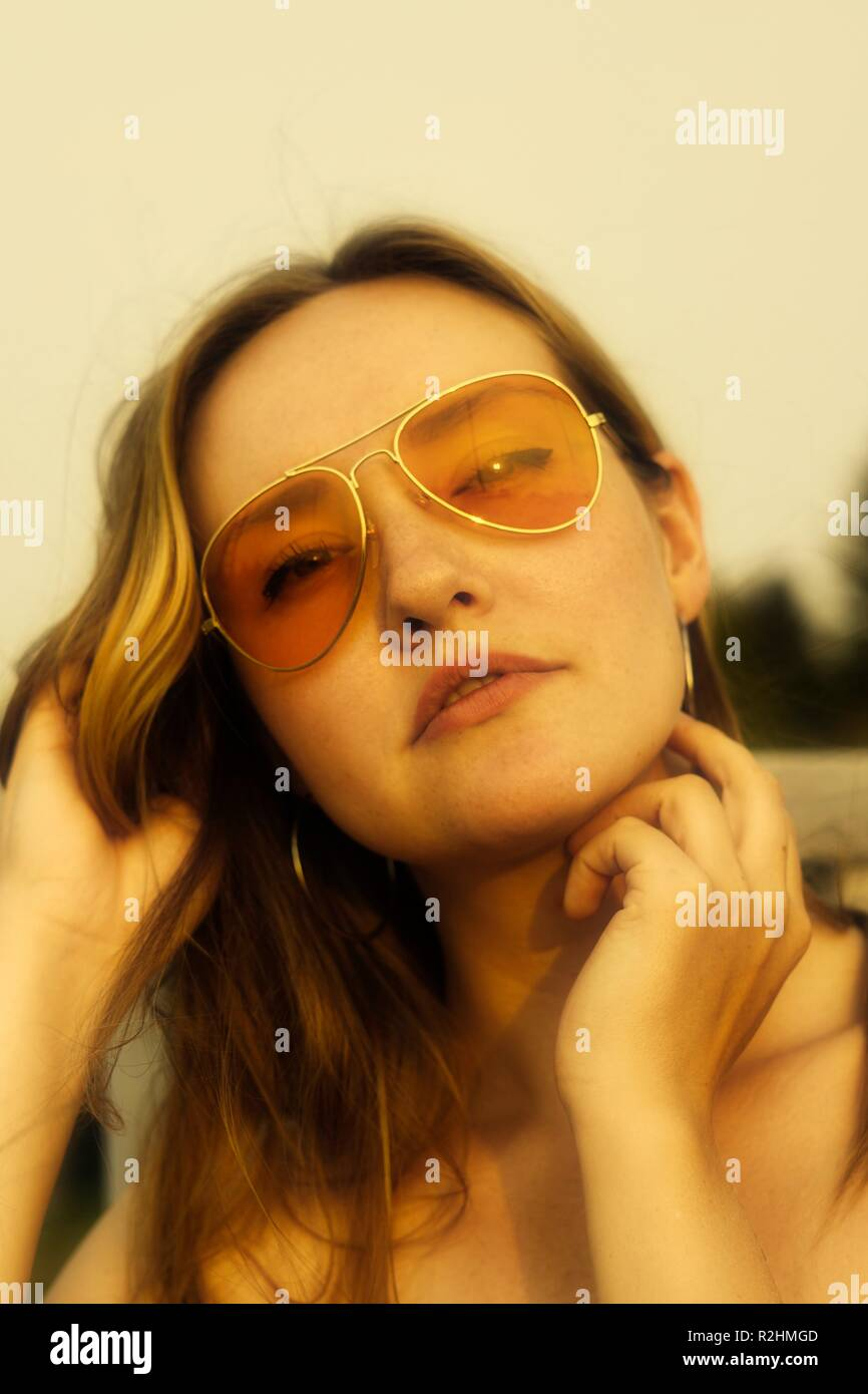 portrait of young woman wearing orange tinted sunglasses with a 70's vibe - Stock Image