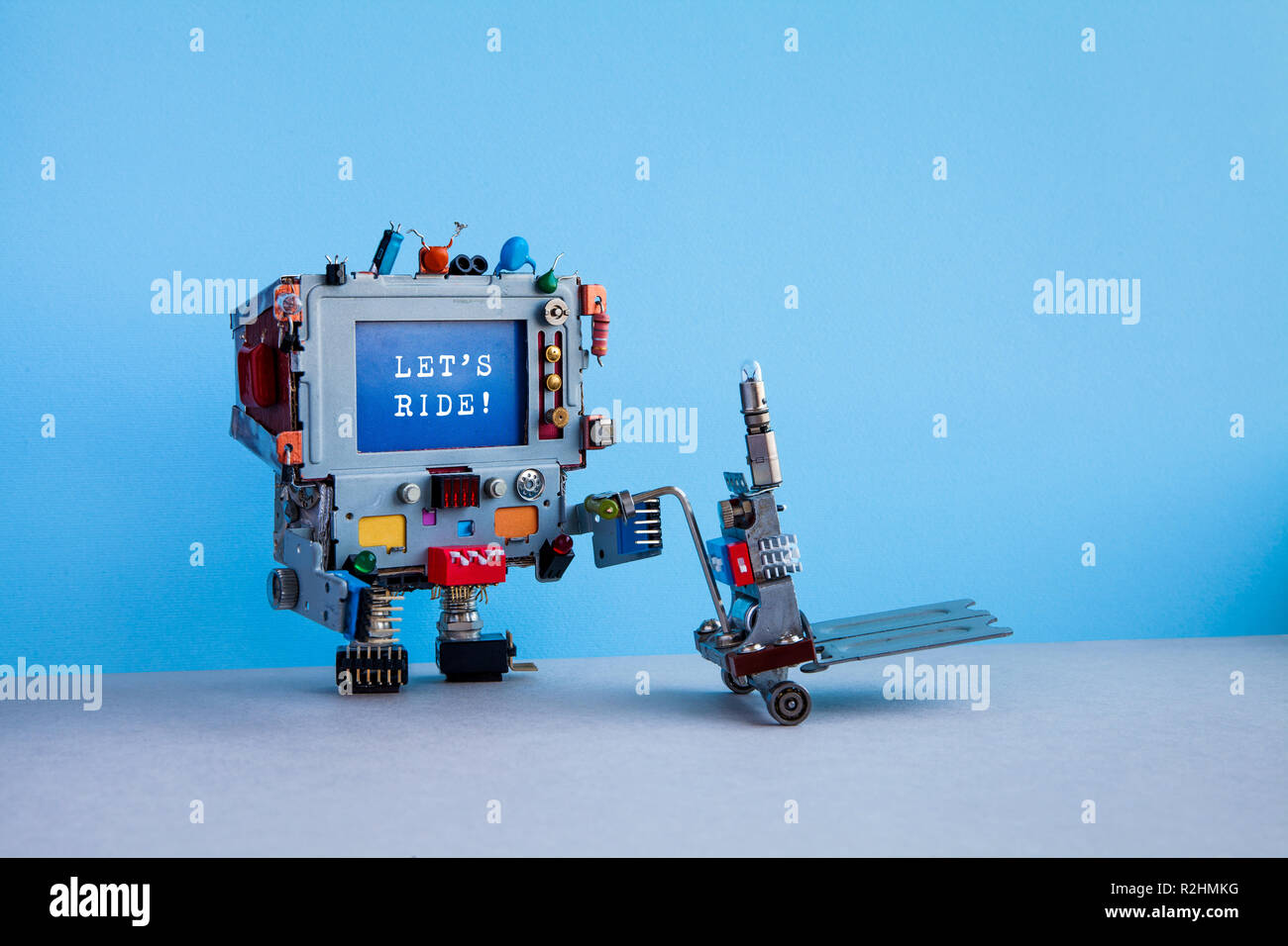 Robotic courier computer and message Lets Ride. Delivery service automation logistic concept. Robot moving pushcart mechanism. Blue wall, gray floor background. copy space. - Stock Image