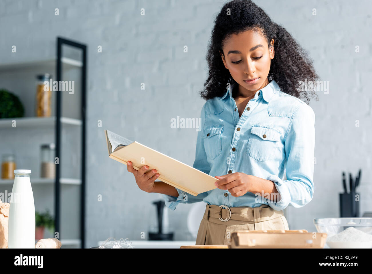 attractive african american girl holding cookbook in kitchen - Stock Image