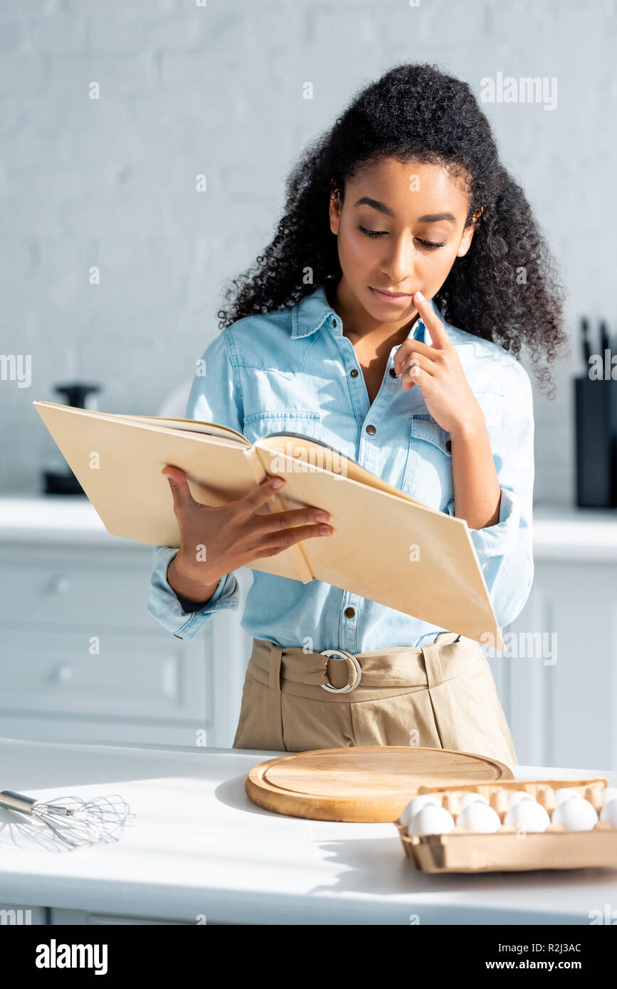 pensive beautiful african american girl reading cookbook in kitchen - Stock Image