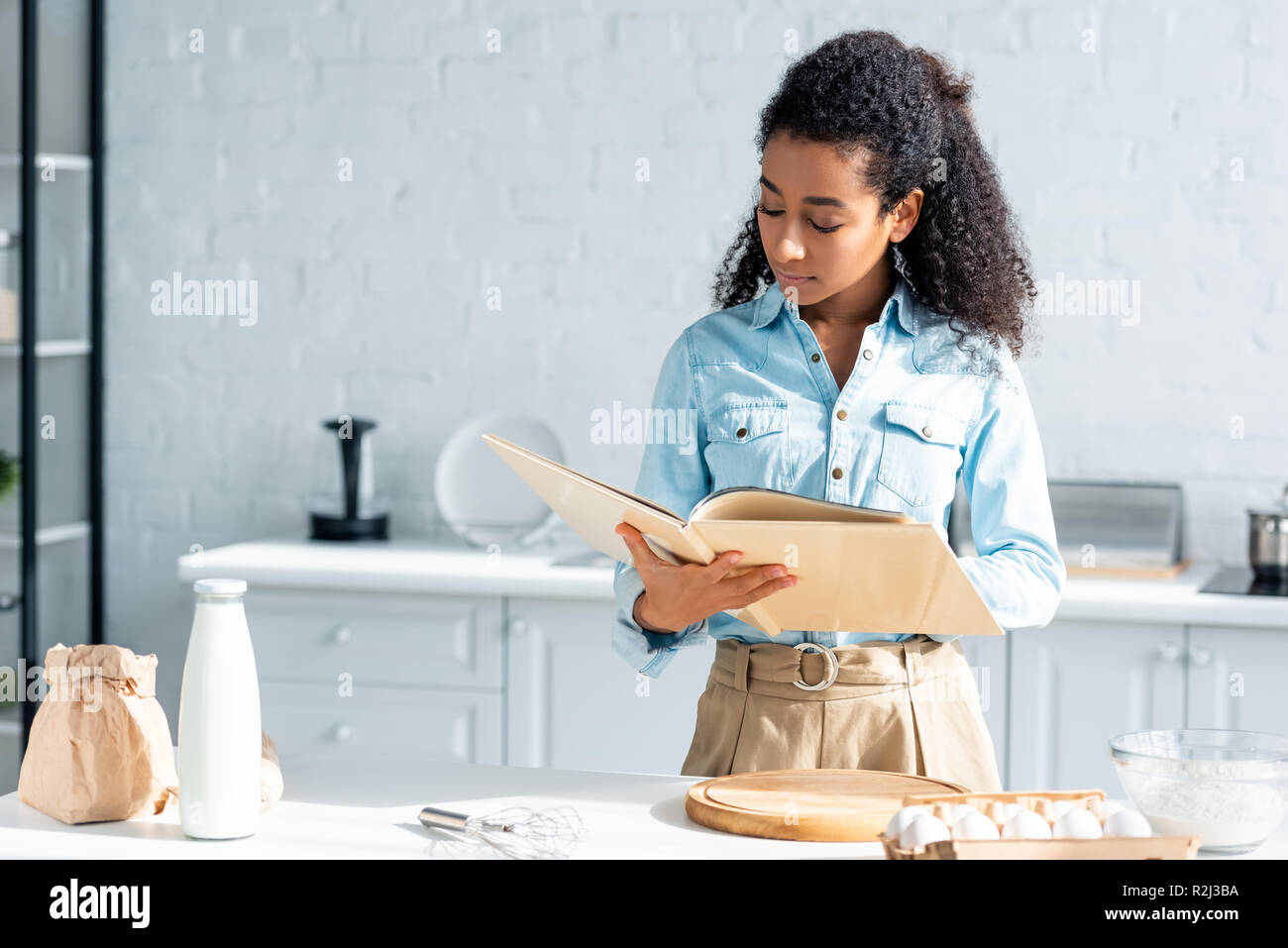 attractive african american woman reading cookbook in kitchen - Stock Image