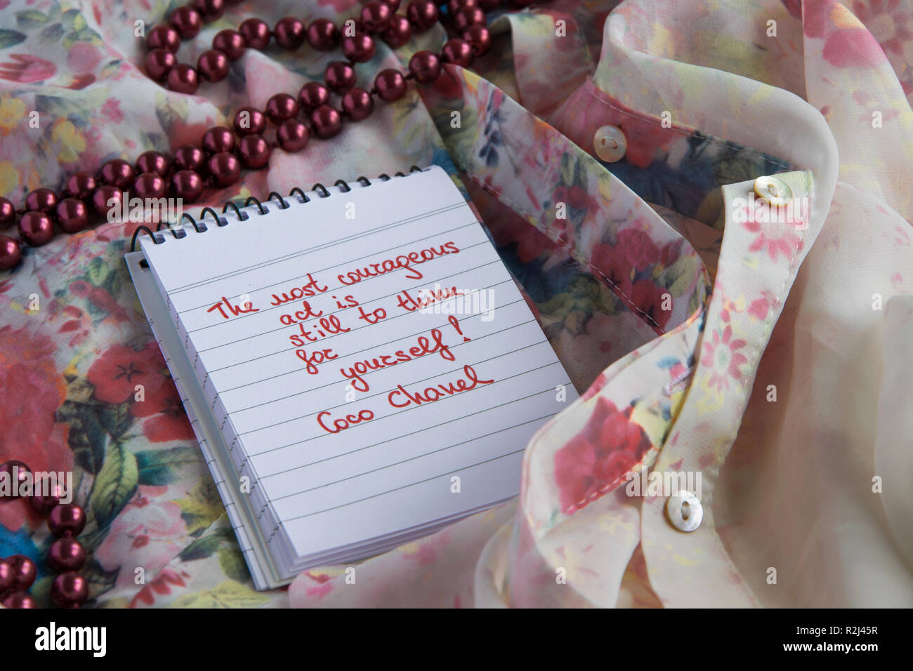 93ef3e8bf Coco Chanel quotes written on a block note, pearl accessories and and silky flower  shirt ,inspiration phrase