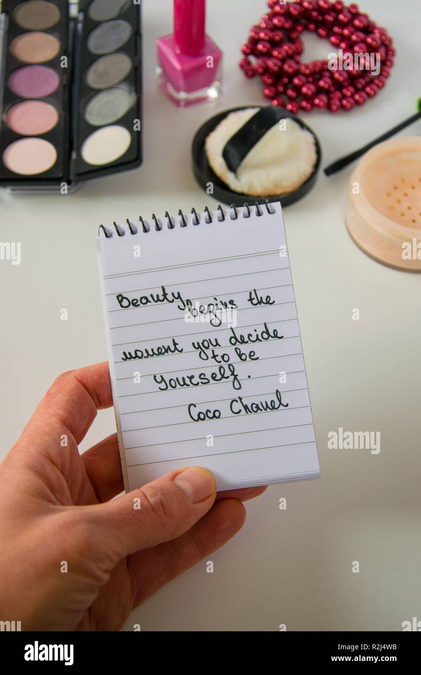 Woman hand holds Coco Chanel quotes written on a block note, pearl accessories and make up on white background, inspiration phrase 'Beauty begins the  - Stock Image