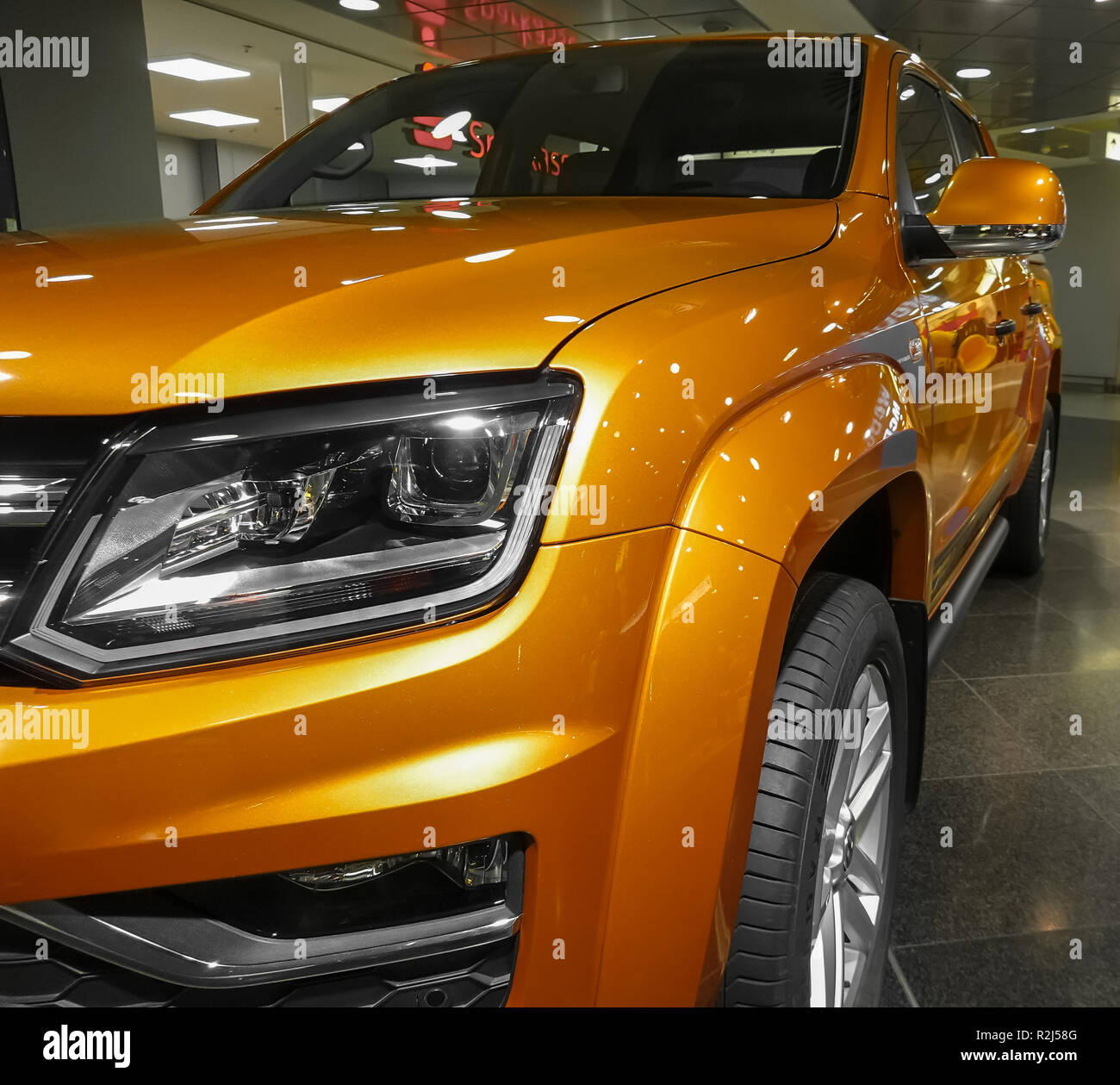 Hannover, Germany, November 19, 2018: Orange colored, almost golden VW Volkswagen Amarok at an exhibition in the airport of Hannover - Stock Image