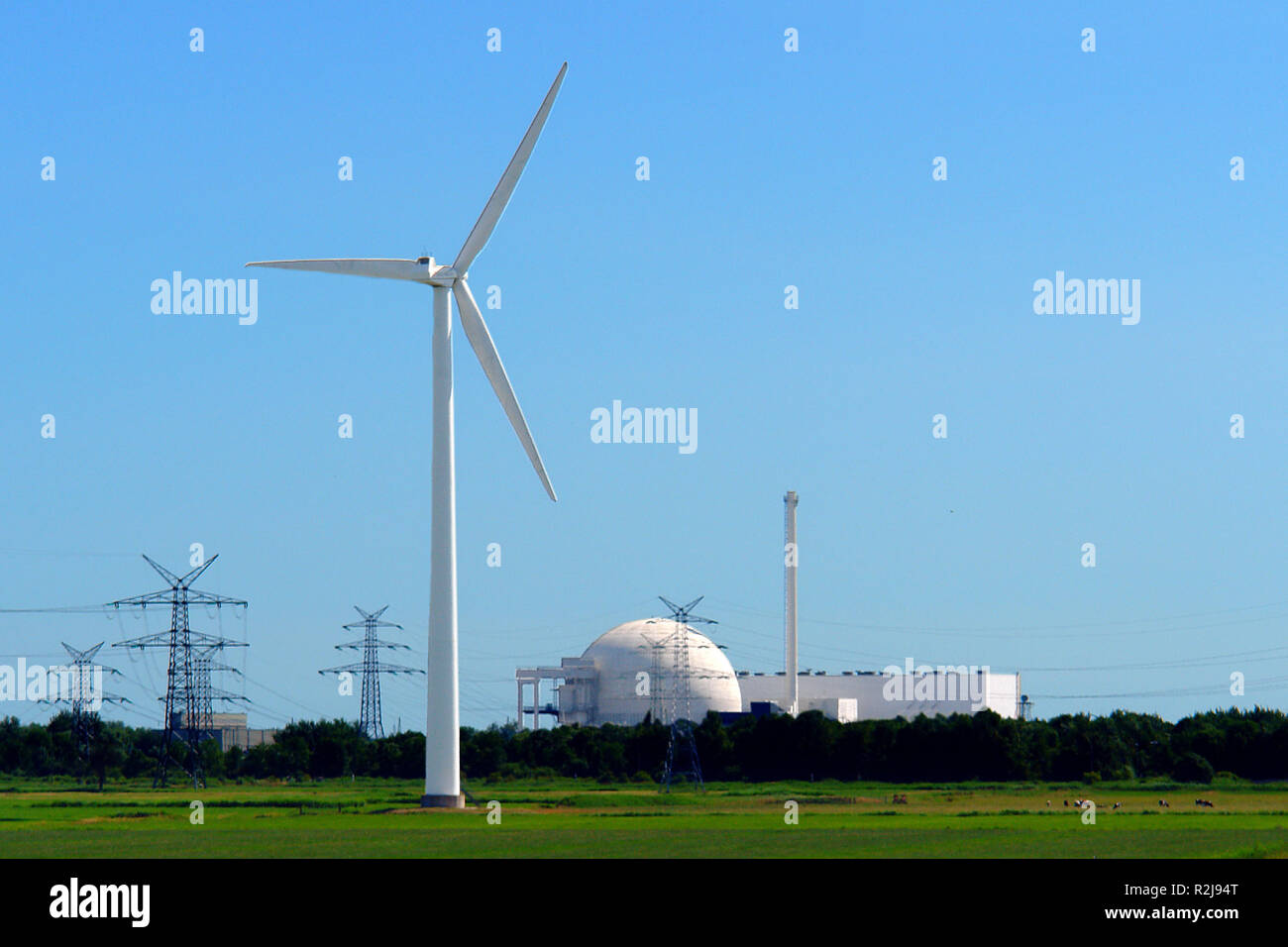 windmill against nuclear power plant unterweser - Stock Image