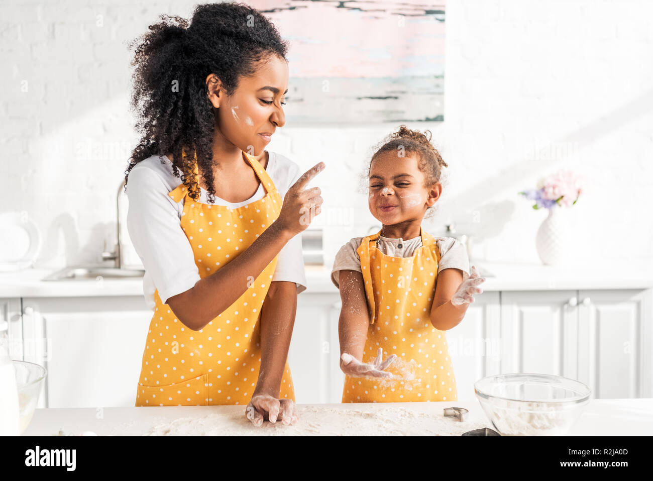 grimacing african american mother and daughter preparing dough and having fun with flour in kitchen - Stock Image