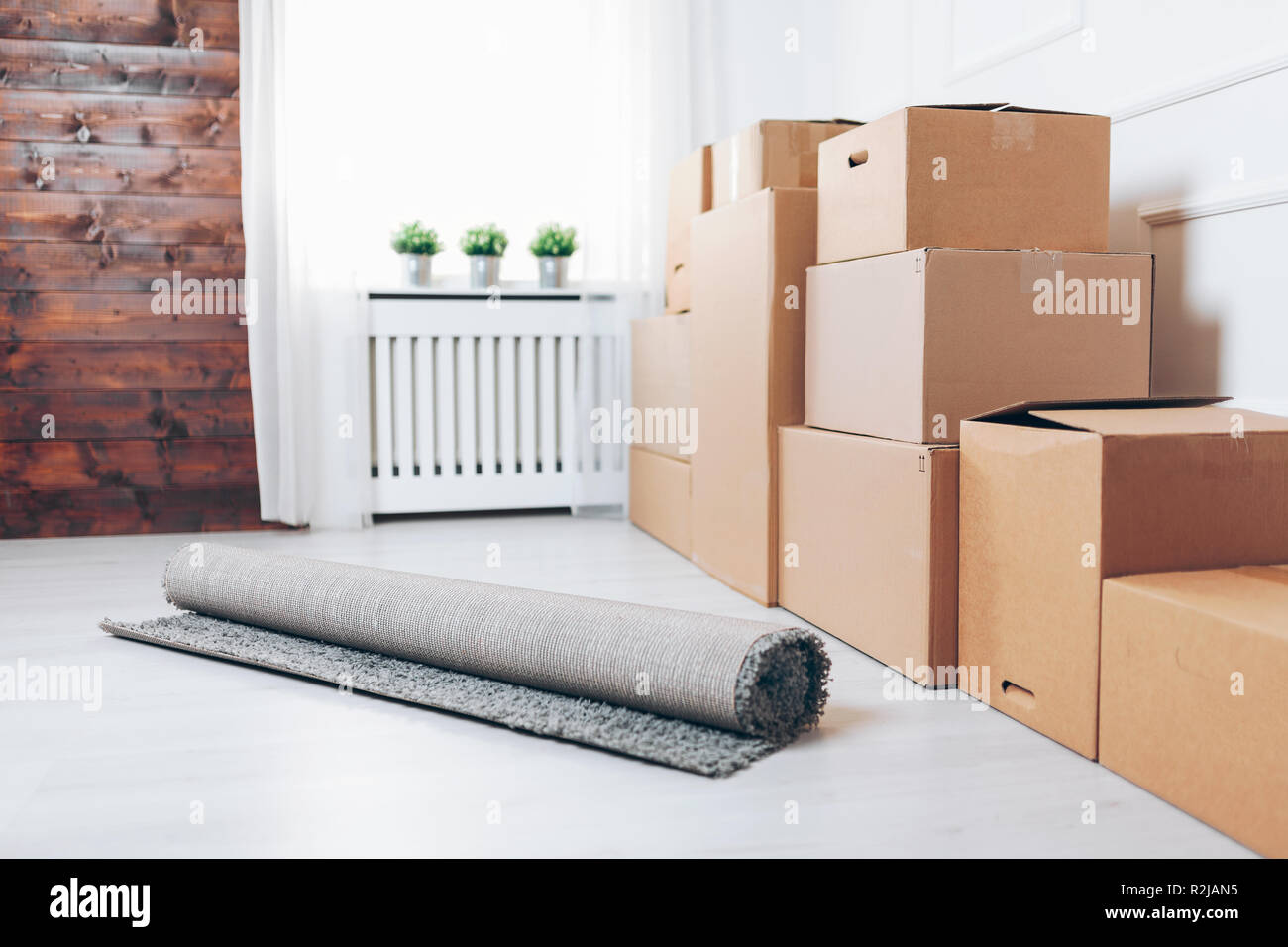 Moving concept. Room full of cardboard boxes - Stock Image