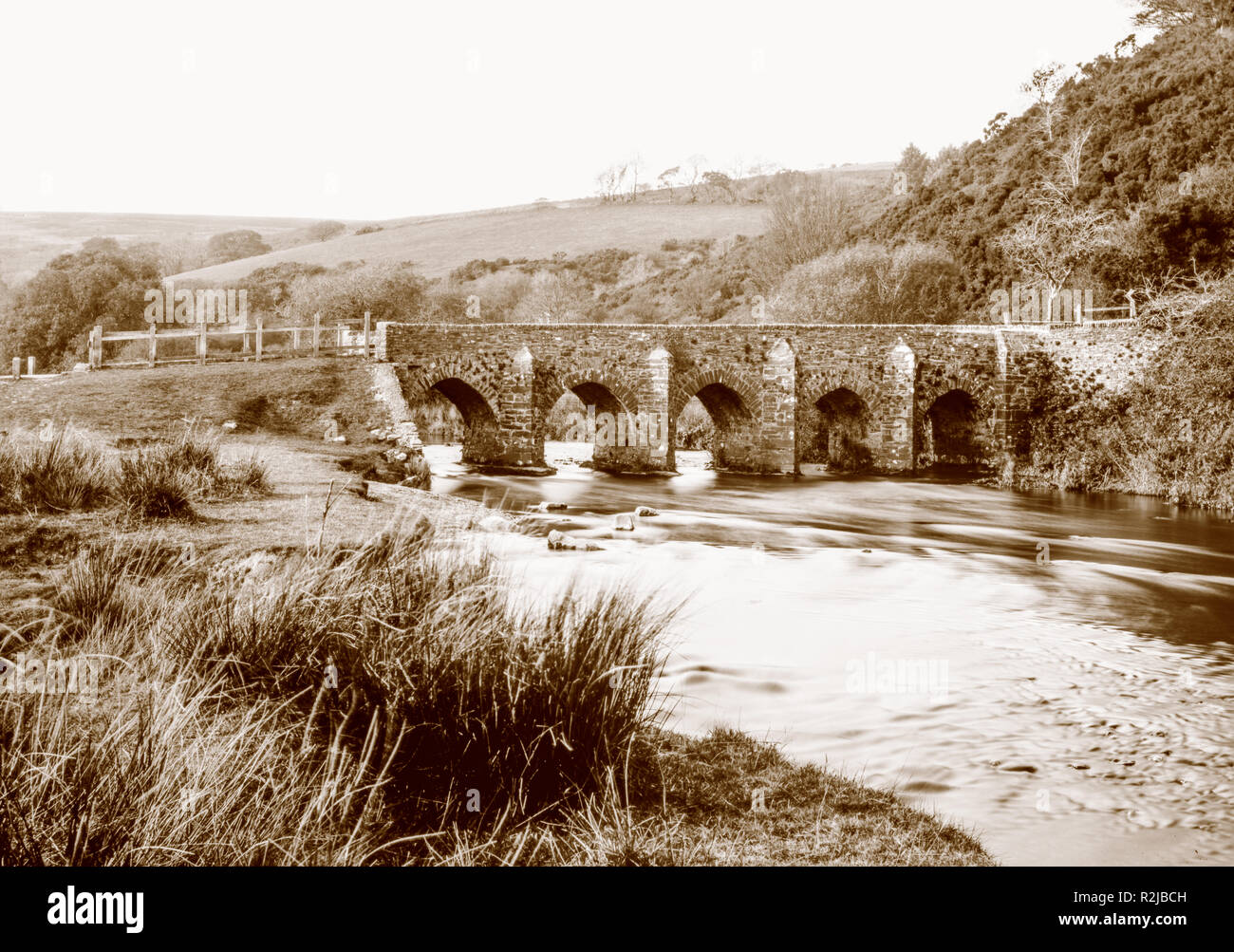 A sepia toned photograph taken on a paper negative in a 7 x 5 inch plate camera in October 2018 of Landacre Bridge over the River Barle on Exmoor - Stock Image