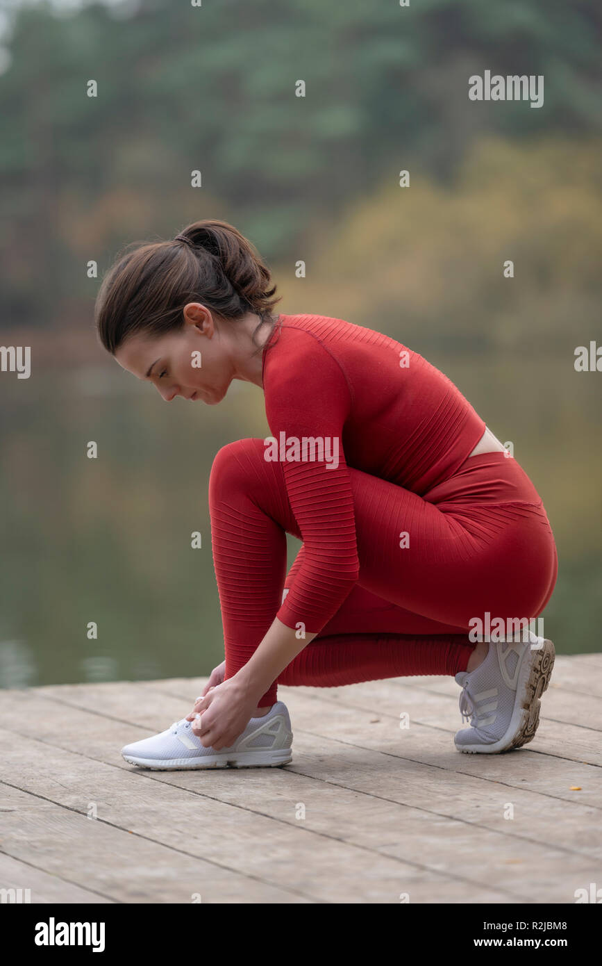 female jogger tying up her shoes before running - Stock Image