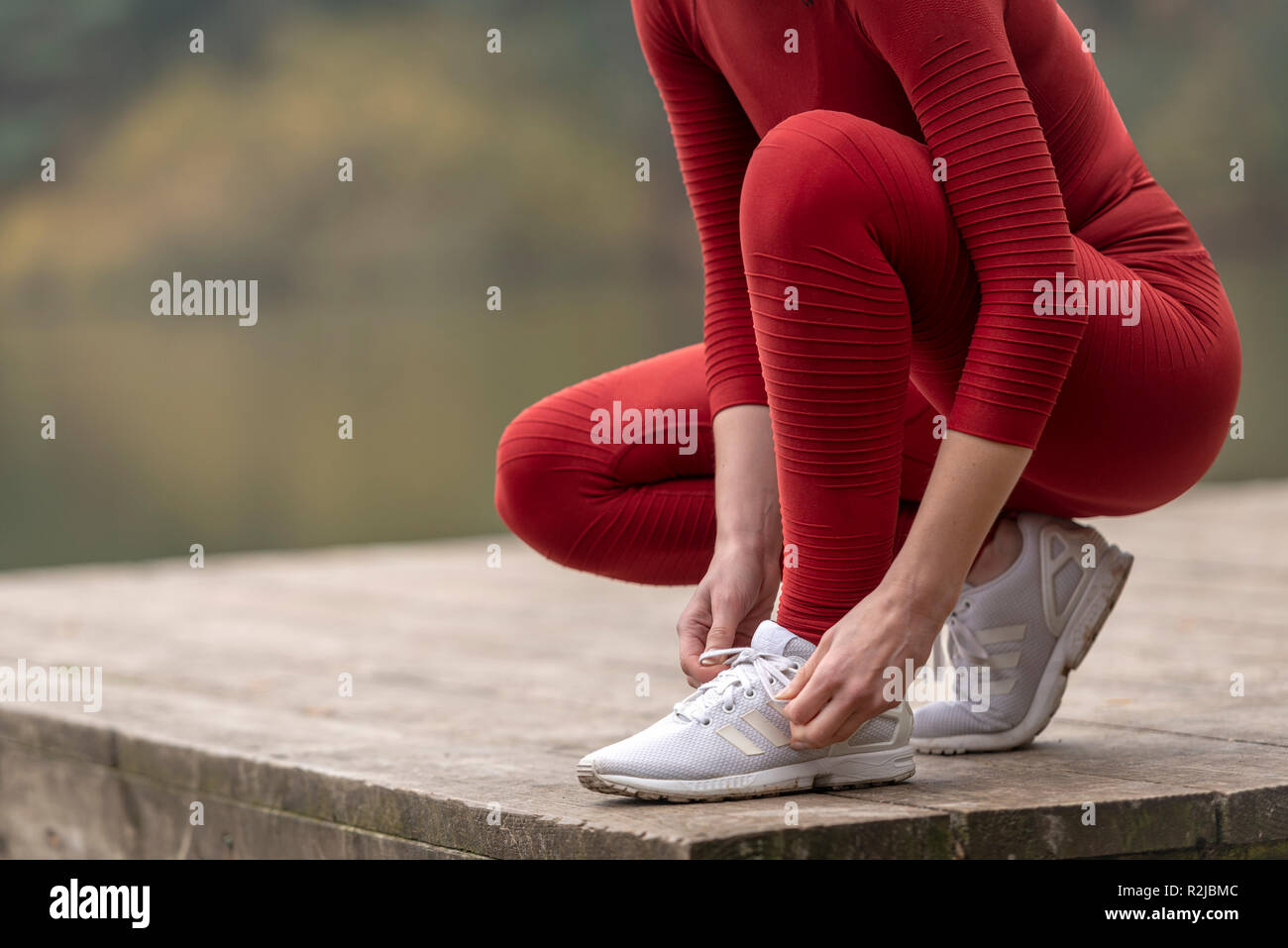 close up of a female jogger tying up her shoes before running - Stock Image