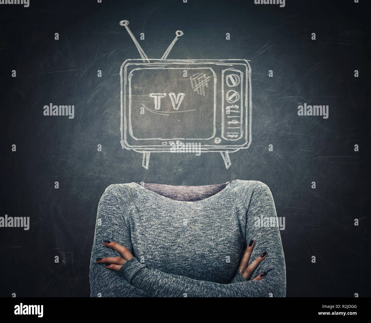 Surreal young addicted woman with crossed arms and tv icon sketch instead of head over blackboard background. Television manipulation and brainwashing - Stock Image