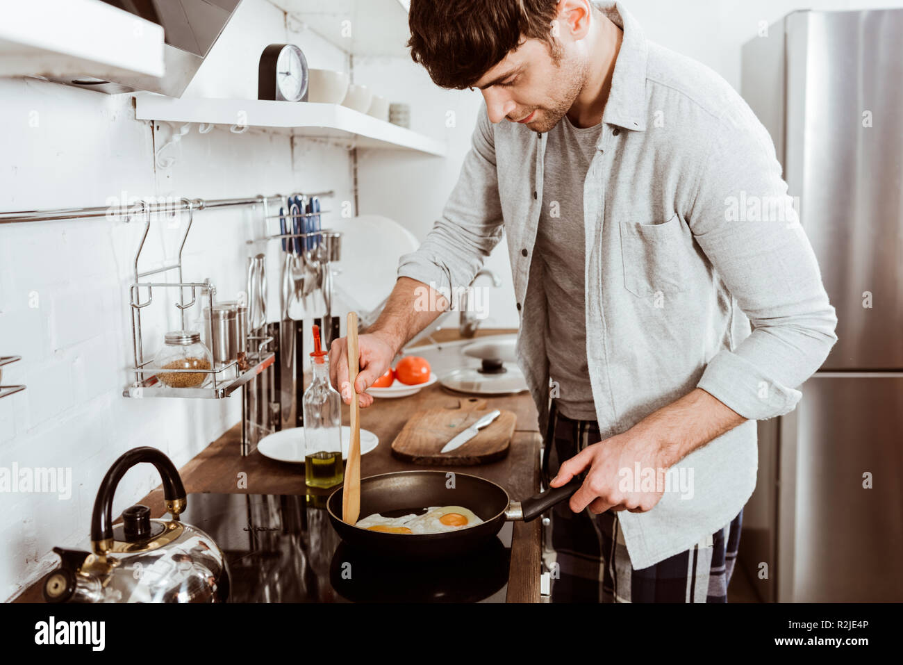 handsome young man making eggs on breakfast in kitchen at home - Stock Image