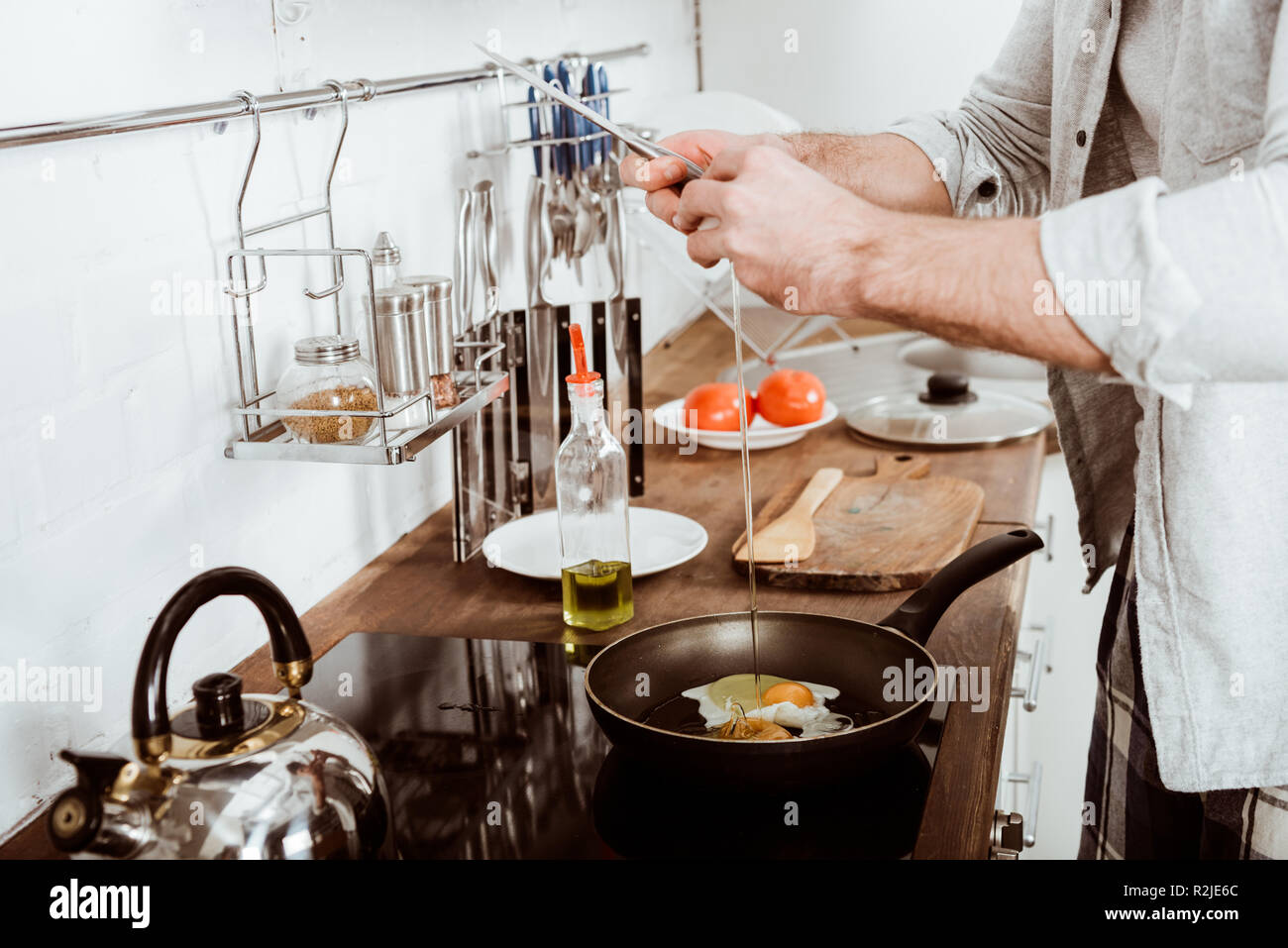 partial view of young man cooking scrambled eggs on breakfast in kitchen - Stock Image