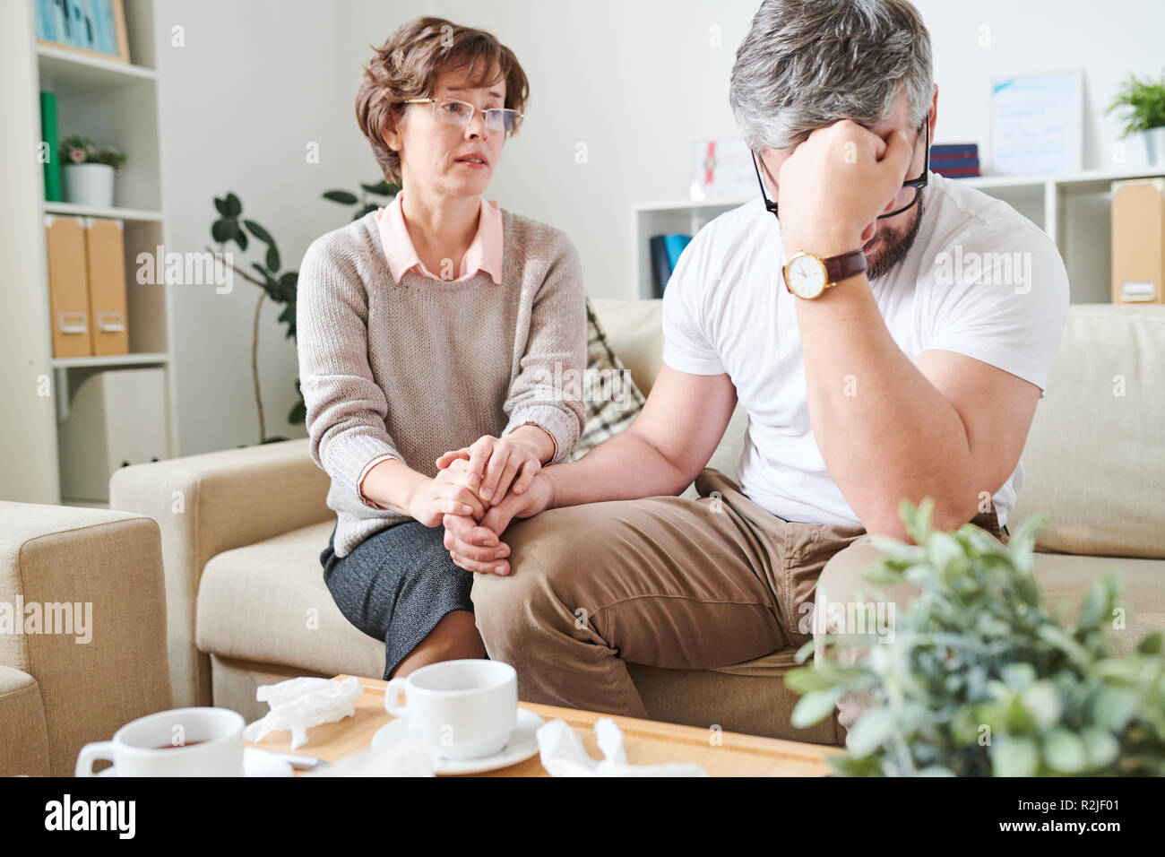 Despaired man coping with emotions at therapy session - Stock Image