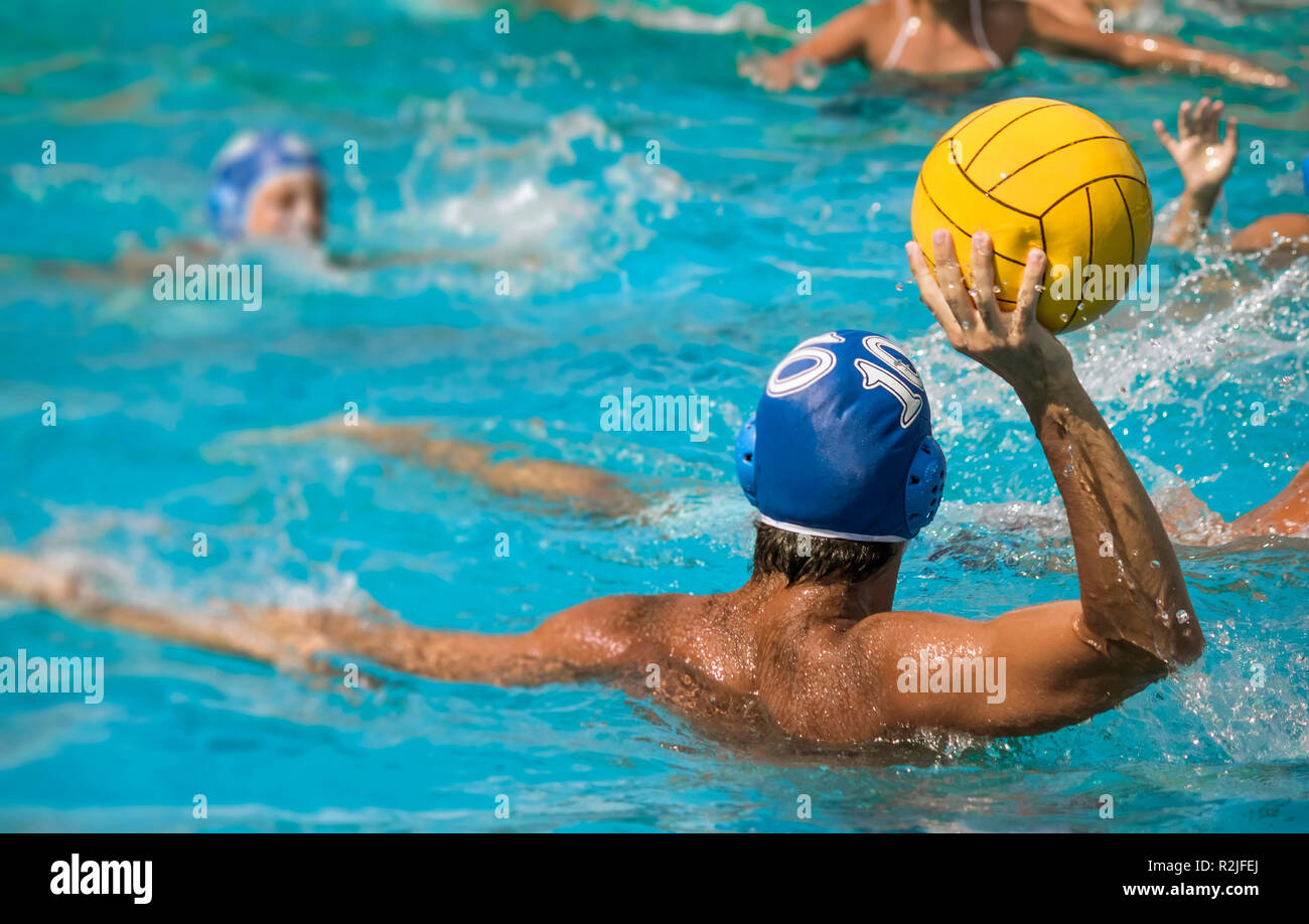 player water polo during a match in pool defences the ball Fromm the pressur of other players - Stock Image