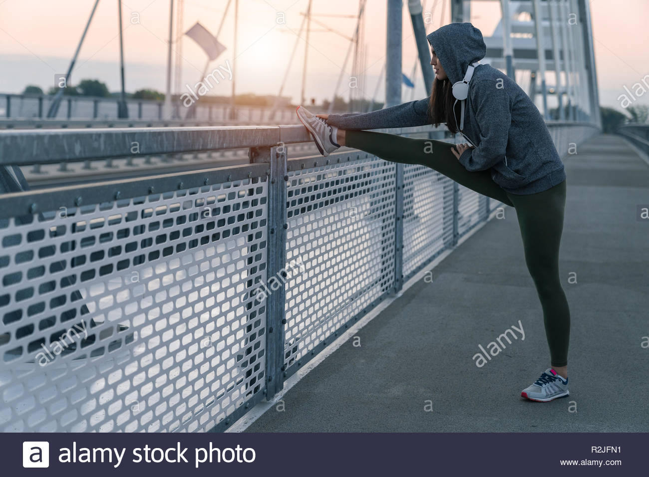 Young sportswoman stretching outdoors on a bridge while looking away in the cold morning - Stock Image