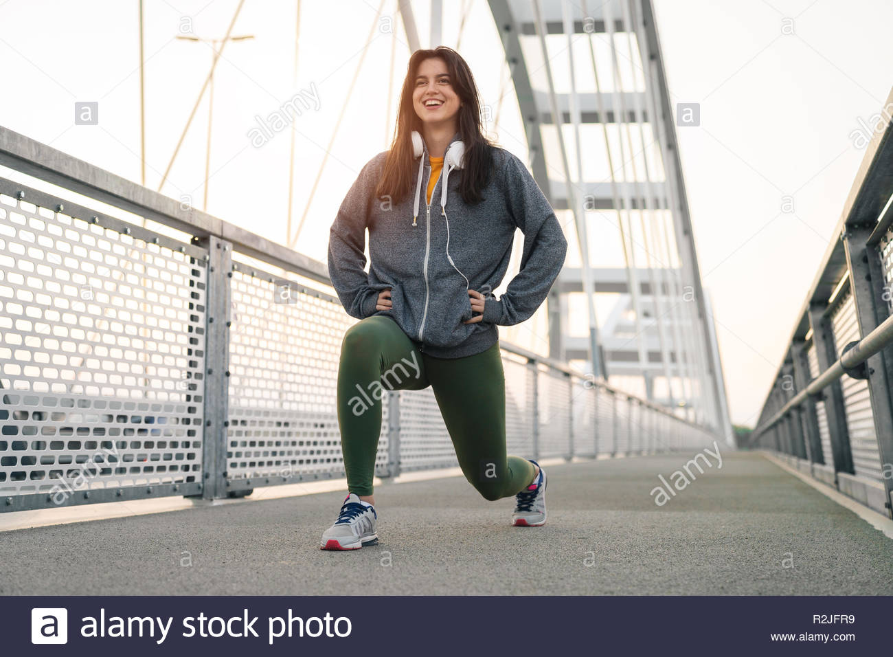 Young sportswoman warming up on a bridge while smiling in the morning. - Stock Image