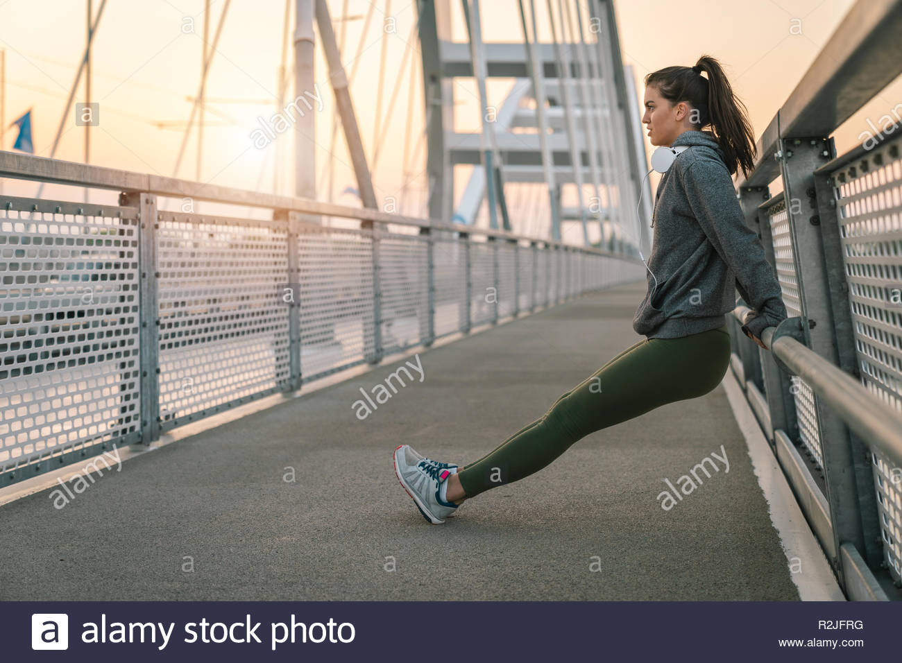 Serious young sportswoman stretching out on a bridge in the morning. - Stock Image