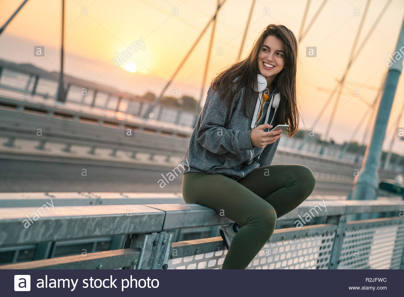 Beautiful young sportswoman smiling while holding a phone outdoors. - Stock Image