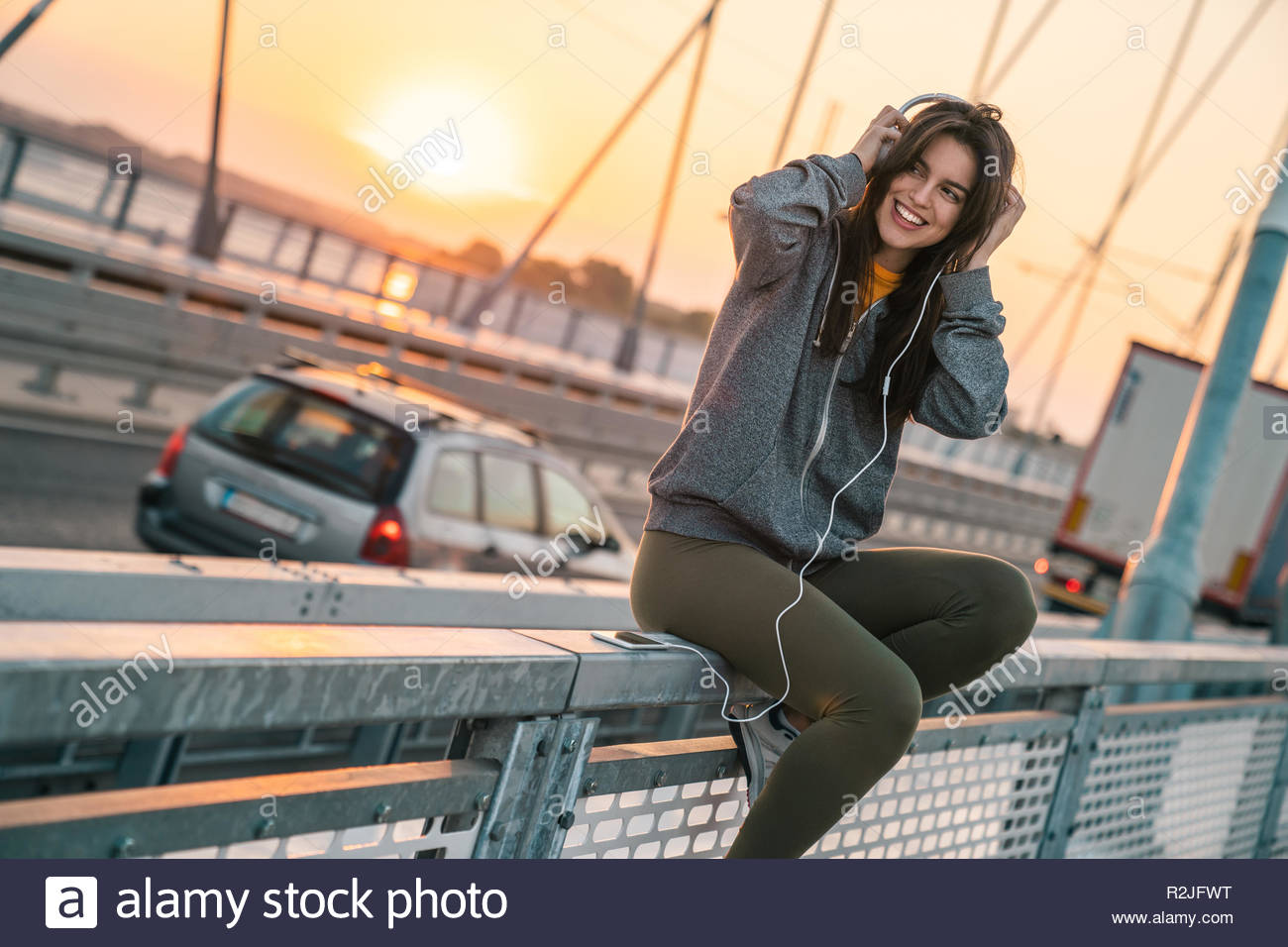 Attractive sportswoman smiling while listening to music on a bridge in the morning. - Stock Image