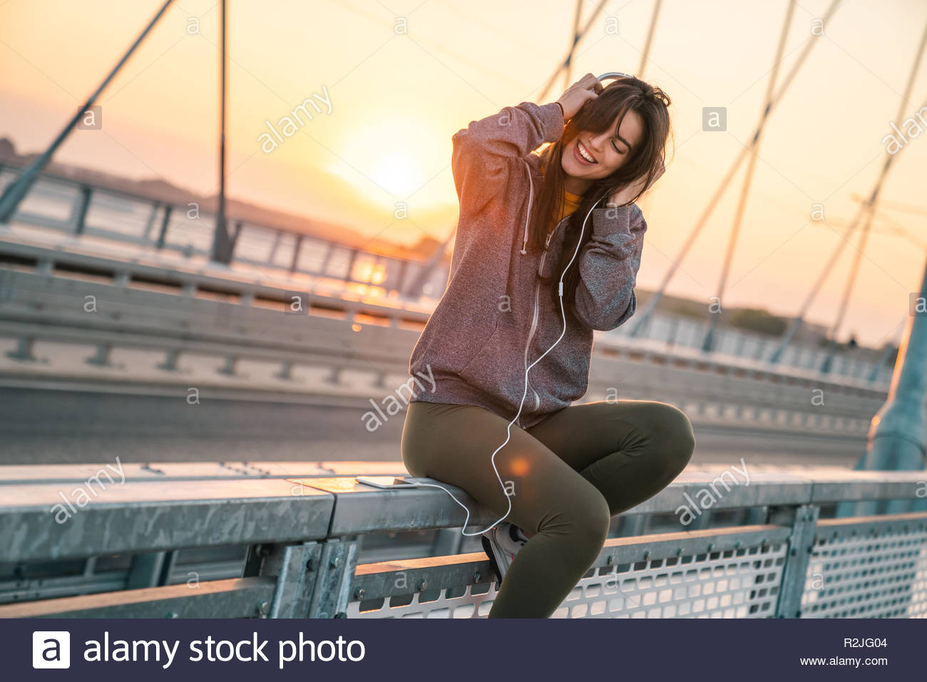 Beautiful young sportswoman smiling while listening to music on a bridge in the morning, - Stock Image