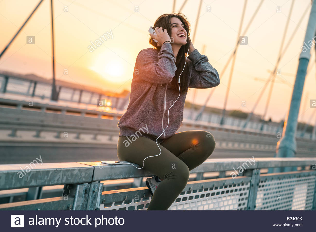 Cheerful young sportswoman smiling while listening to music while sitting on a bridge in the morning. - Stock Image