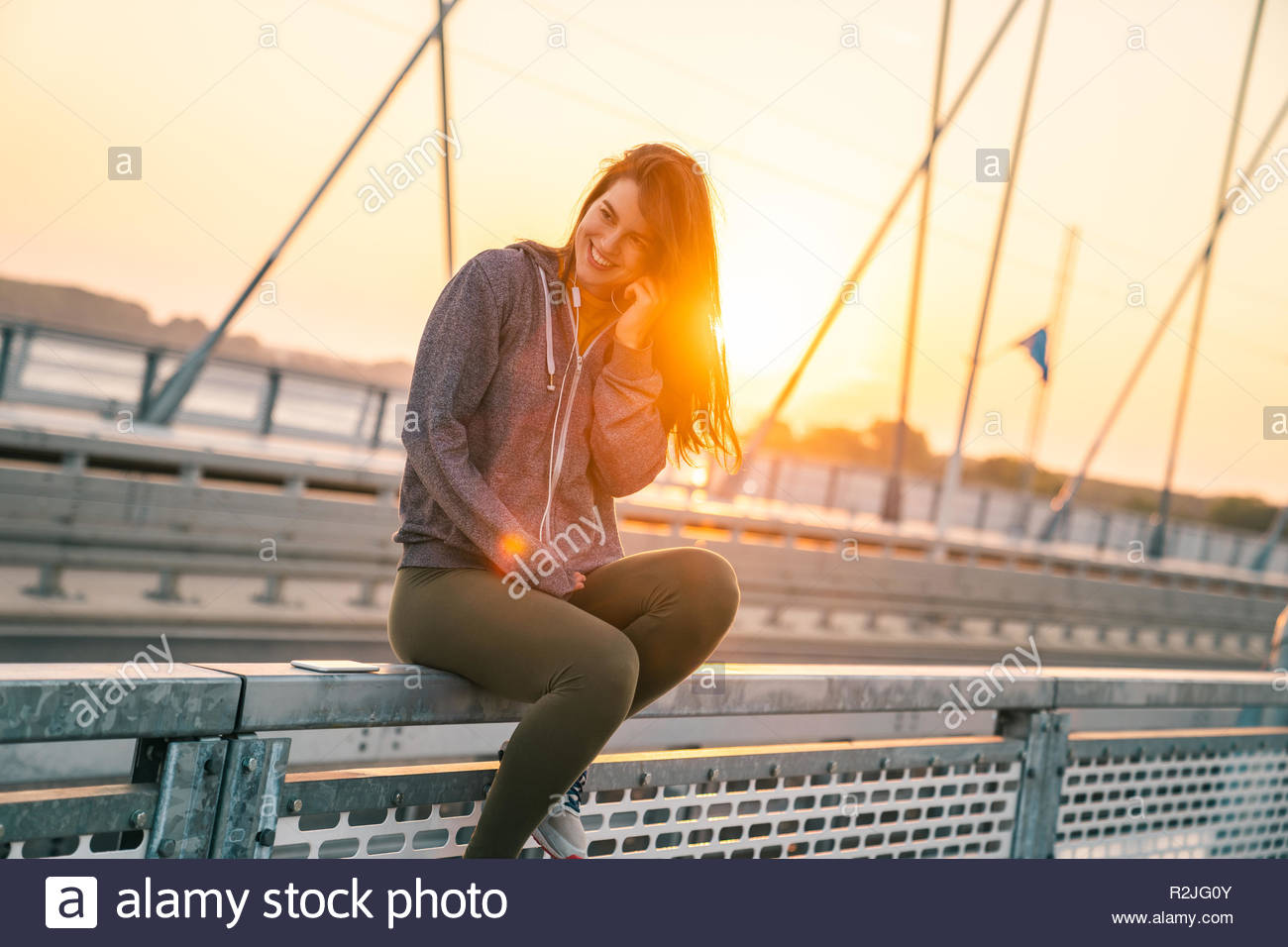 Happy sportswoman listening to music at sunrise on a bridge in the morning. - Stock Image