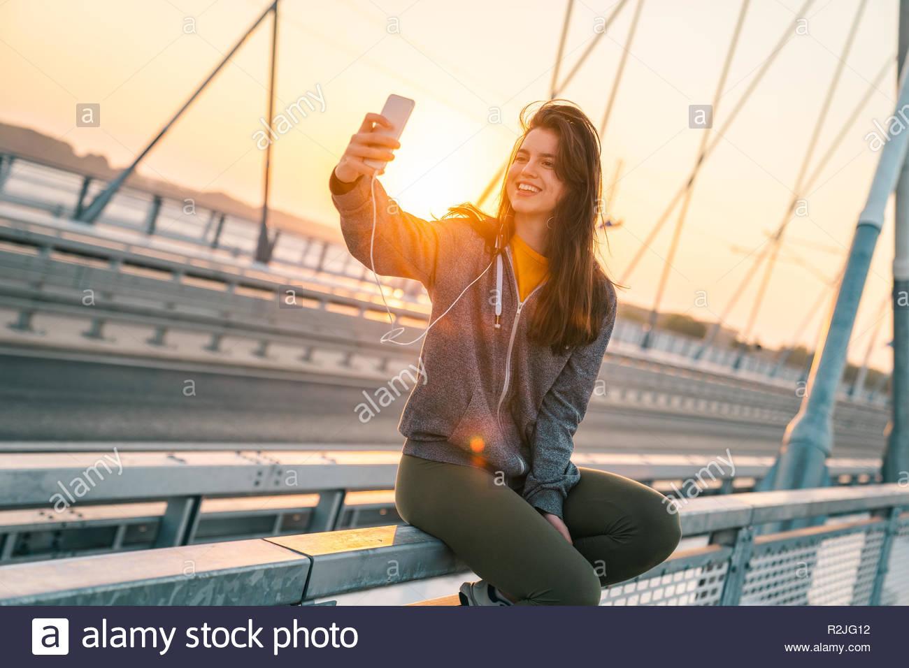 Beautiful sportswoman taking a selfie while sitting on the bridge at sunrise. - Stock Image