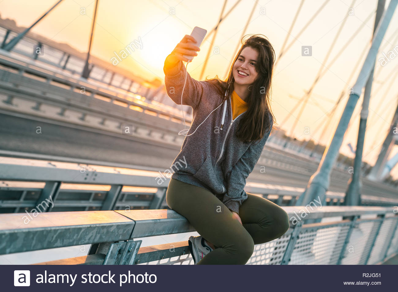 Young attractive sportswoman taking a selfie while sitting on the bridge at sunrise. - Stock Image