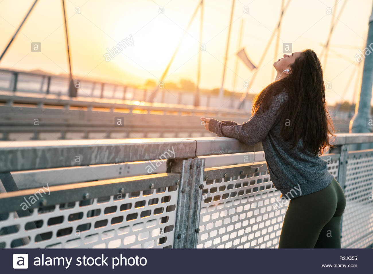 Young sportswoman relaxing while listening to music on earphones at sunrise. - Stock Image