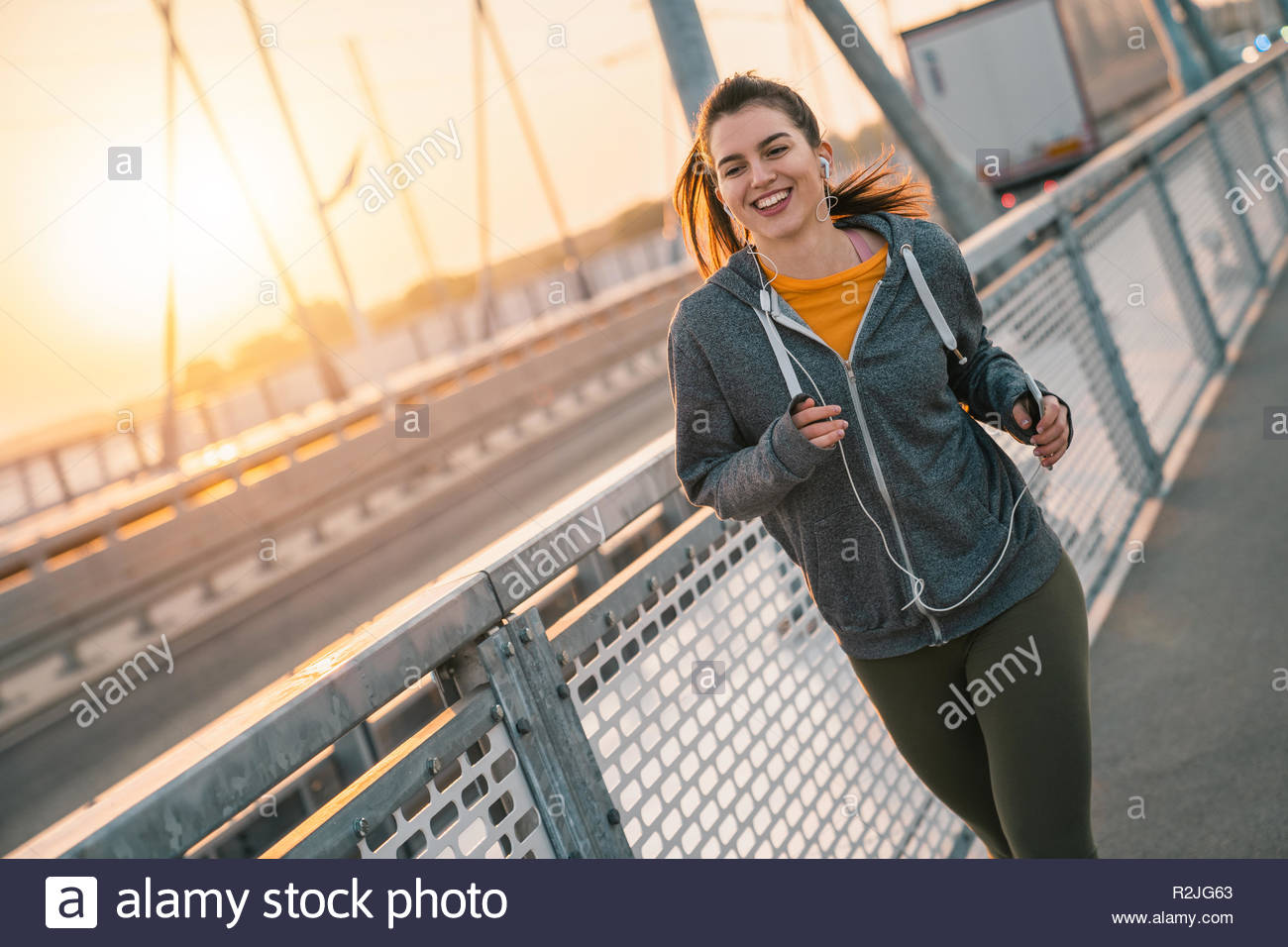 Young sportswoman running while smiling and listening to music on a bridge at sunrise. - Stock Image