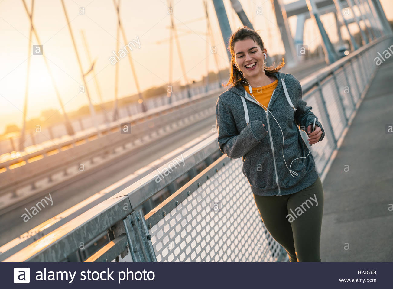 Young sportswoman jogging while smiling and listening to music on a bridge at sunset. - Stock Image