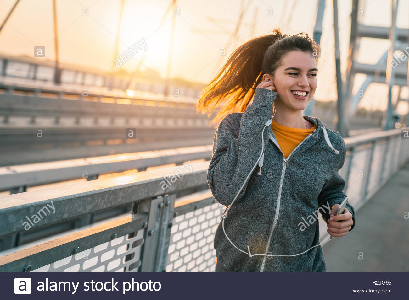 Happy sportswoman listening to music on earphones while jogging on a bridge at sunrise. - Stock Image