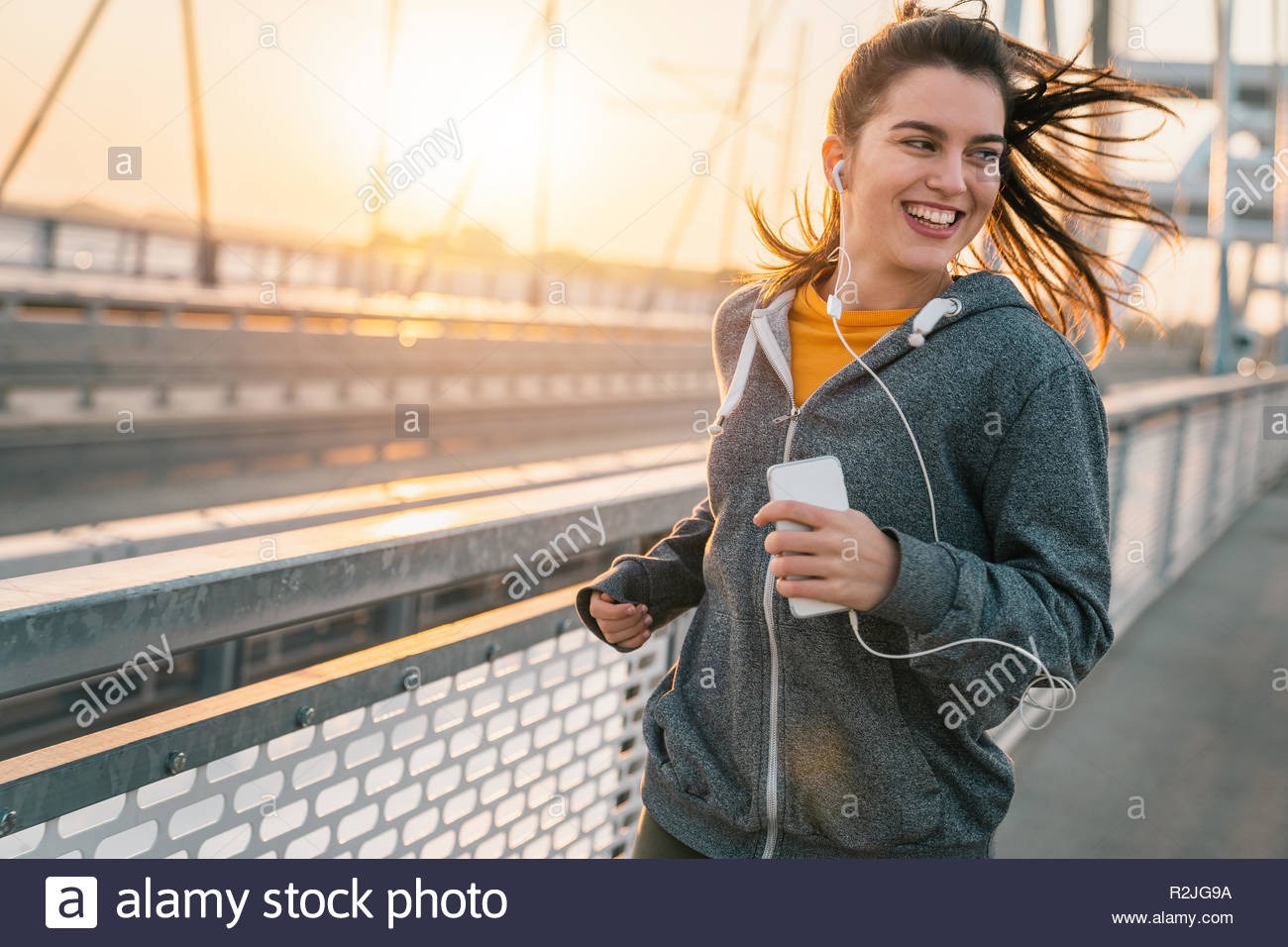 Cheerful sportswoman listening to music on earphones while jogging on a bridge at sunrise. - Stock Image