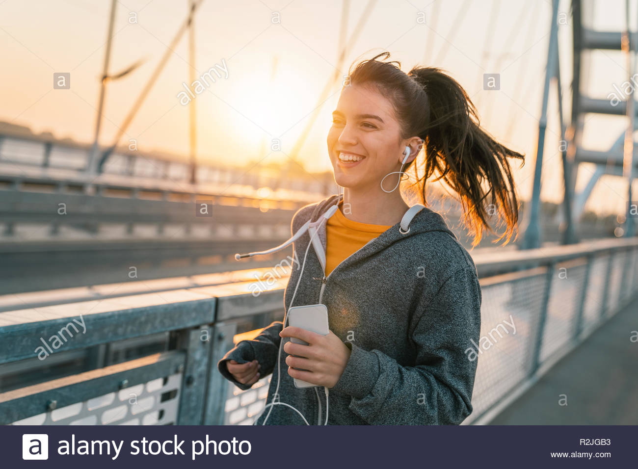 Attractive sportswoman smiling while listening to music and jogging on a bridge at sunrise. - Stock Image