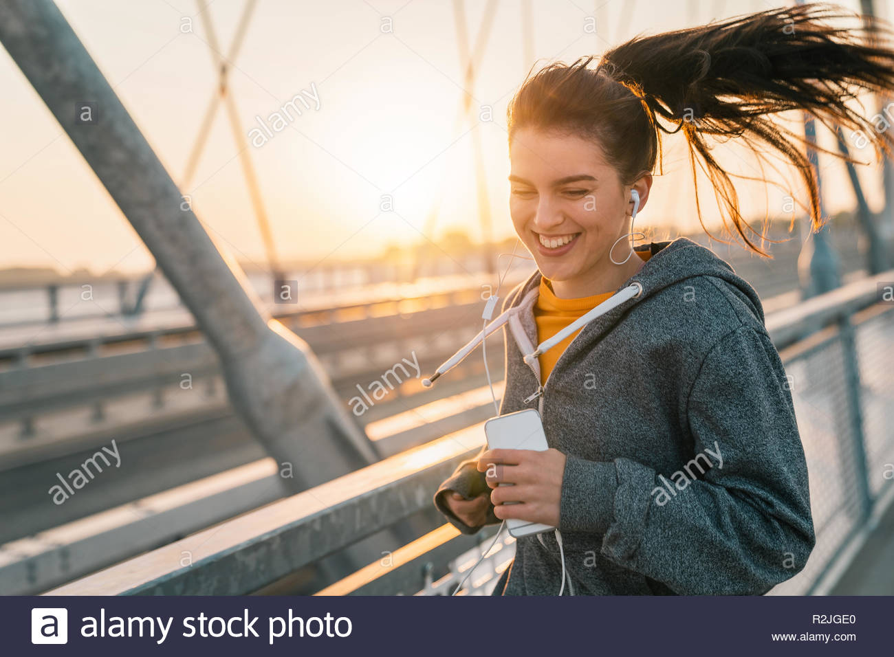 Sportswoman running while listening to music and smiling on bridge at sunrise. - Stock Image