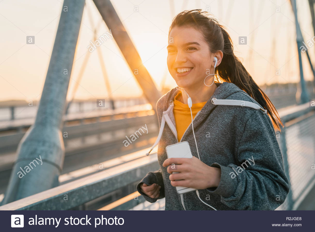 Young sportswoman jogging while smiling and listening to music on a bridge at sunrise. - Stock Image