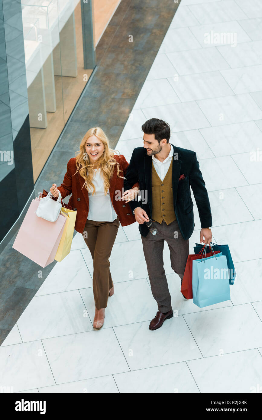 a37dfcd255 overhead view of happy couple with shopping bags walking in shopping mall -  Stock Image