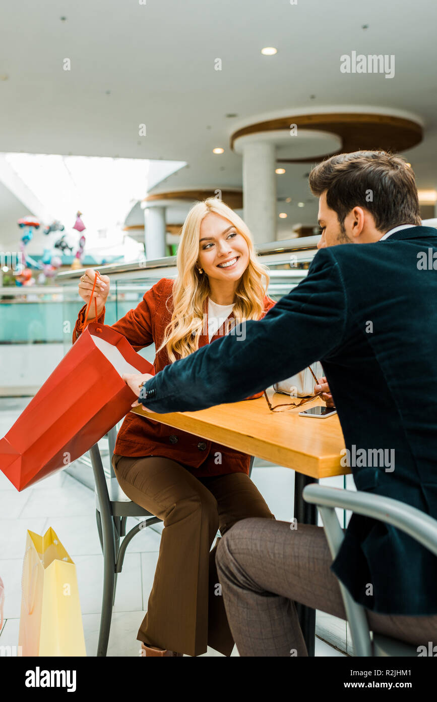 smiling woman showing something in shopping bag to boyfriend while sitting in cafe in shopping center Stock Photo